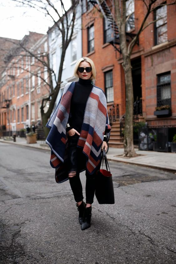all black outfit with a bold geometric blanket scarf as a shawl