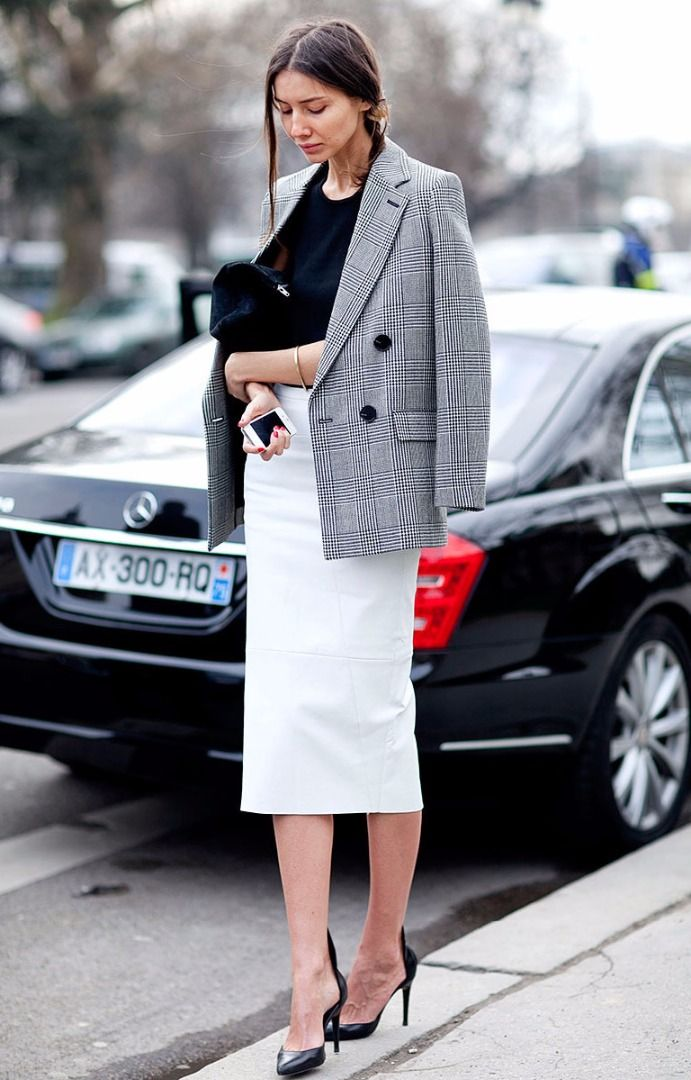 white midi skirt, a black top, heels and a tweed jacket