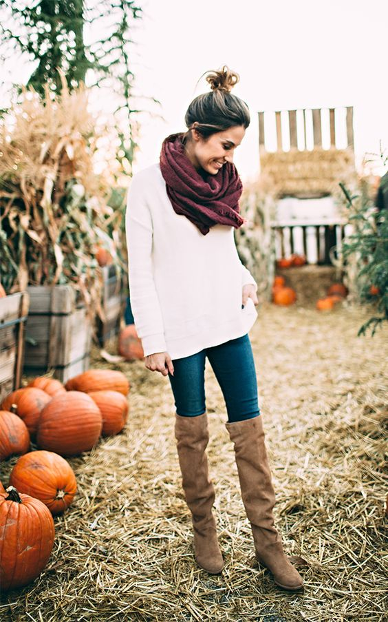 white sweater, a pruple scarf and tall brown suede boots