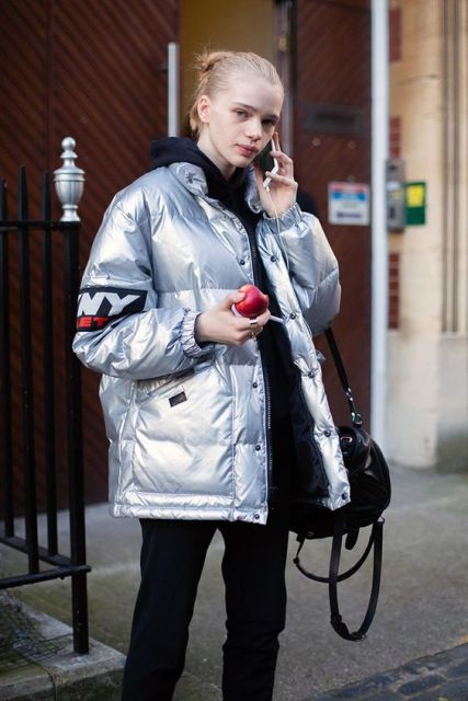 Metallic puffer jacket with black clothes and bag
