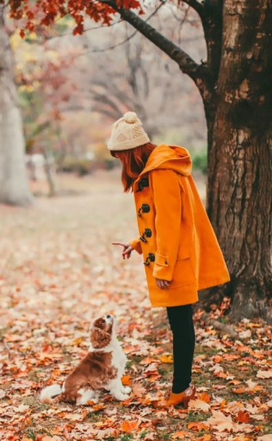 Orange coat with beige beanie, black pants and brown ankle boots
