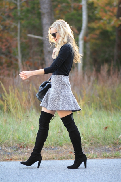 With black shirt and black thigh high boots