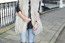 With black shirt, fur vest and jeans