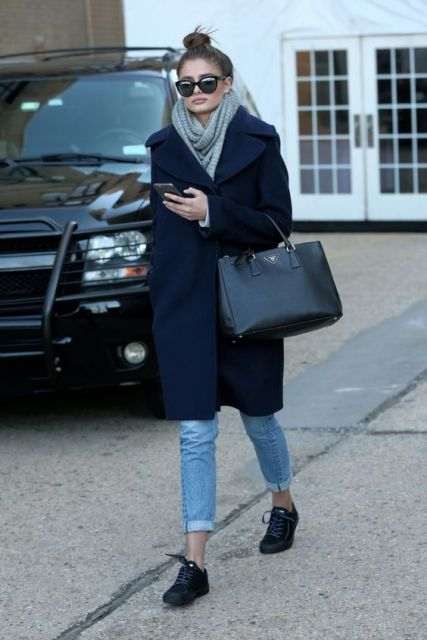 With cuffed jeans, black shoes, leather black bag and oversized scarf
