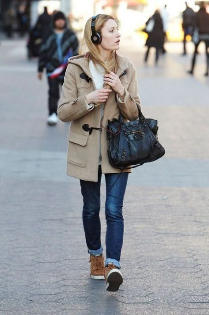 With cuffed jeans, brown boots and black bag