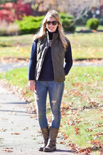 With distressed jeans, sweater and puffer vest