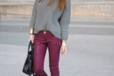 With gray loose sweater, black boots and leather bag