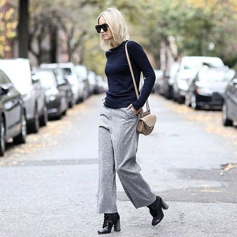 With loose sweater, ankle boots and small bag