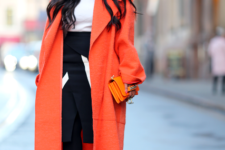 With orange fur hat, white turtleneck, black and white skirt, black tights and printed ankle boots