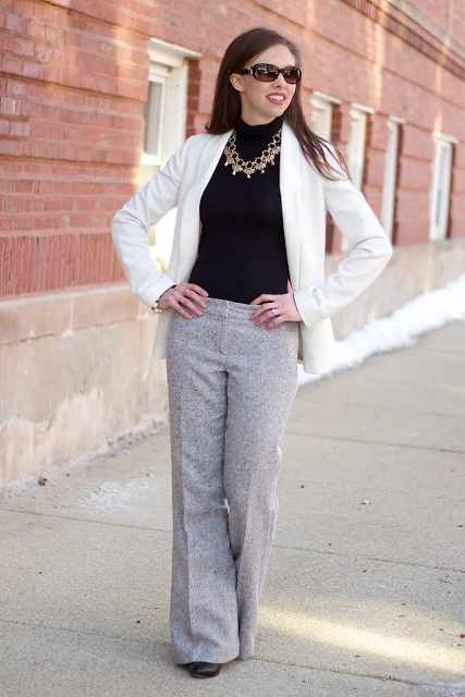 With turtleneck, statement necklace and white jacket
