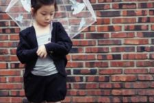 black shorts, a black cardigan, leg warmers and rain boots