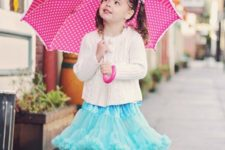pink printed rain boots, a ruffled blue skirt and a white cardigan
