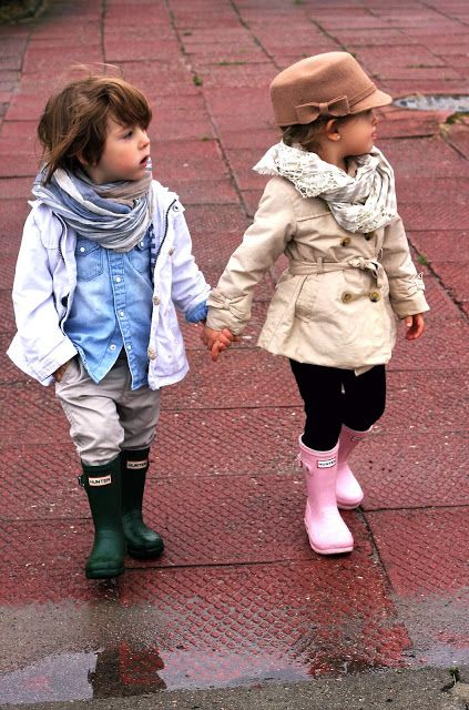 pink rain boots, black pants, a neutral raincoat and  a hat