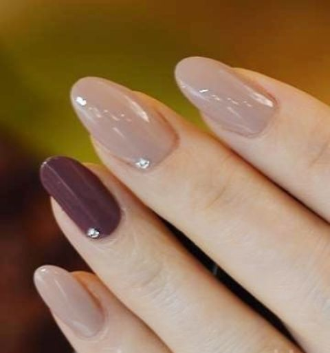 neutral fall nails with beads and a burgundy accent one