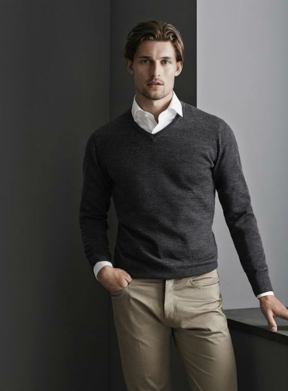 grey pullover, a white shirt, grey pants and no tie