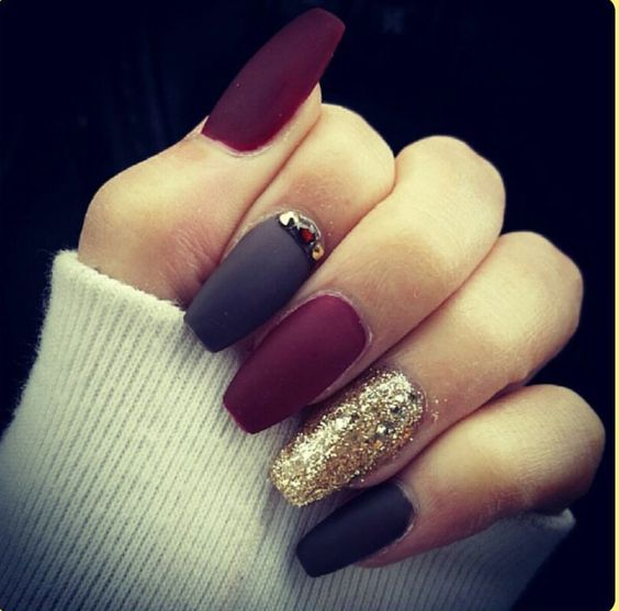 matte manicure in black and red with a gold accent nail