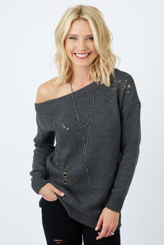 off the shoulder sweater with metal rings and black ripped jeans