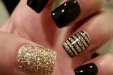 13 black and gold manicure with a gold nails and a striped accent one