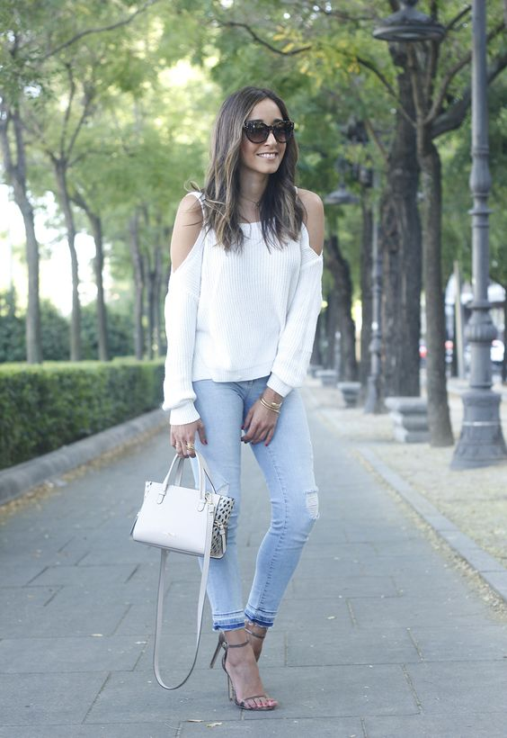 ripped blue jeans, a white off the shoulder and heels