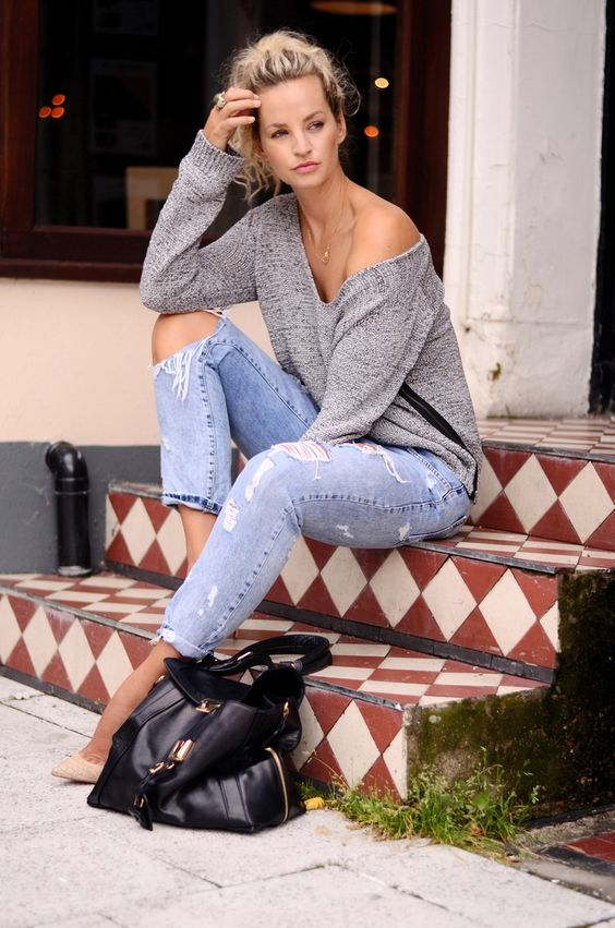 ripped jeans, a grey off the shoulder sweater and nude heels