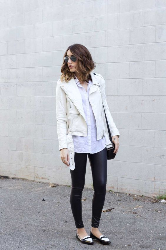 a white moto jacket, a white button down shirt and black leather leggings