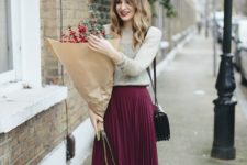 15 pleated burgundy midi skirt, mid-calf boots, a neutral sweater and a corss body bag