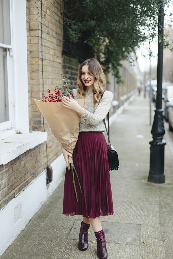 pleated burgundy midi skirt, mid calf boots, a neutral sweater and a corss body bag