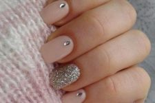 picture of long neutral nails with a glitter accent