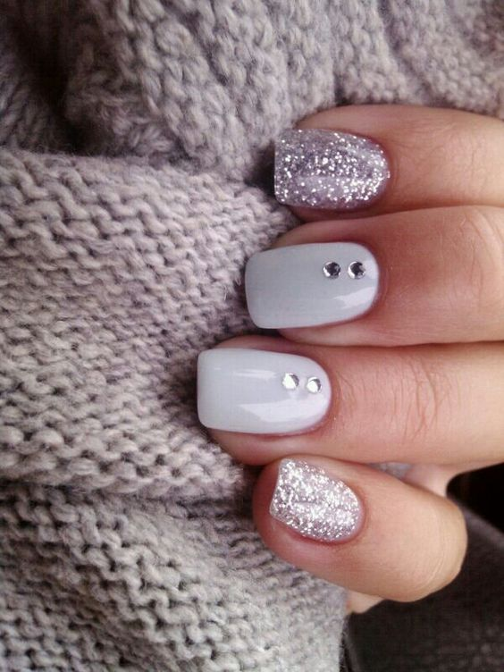 modern manicure with two glitter nails and white ones with beads