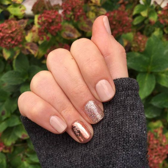 neutral nails with glitter and a copper accent one