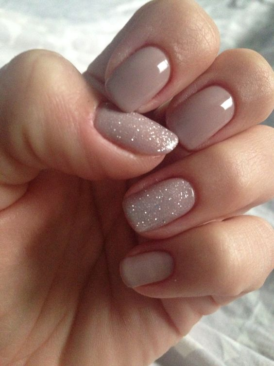 neutral manicure with two glitter accent nails