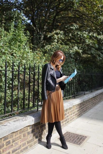 ocher pleated midi, black tights and shoes, a navy top and a black leather jacket