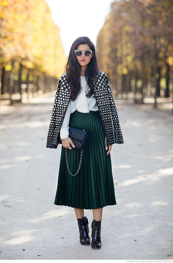 studded leather jacket, a plissed midi skirt in dark green, a white collared shirt, black ankle boots