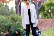 25 black boots, a neutral oversized cardigan and a black top