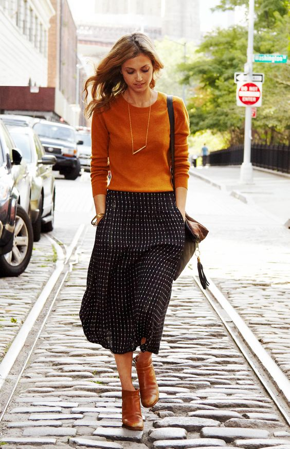 patterned midi, an ocher sweater and boots for a casual look