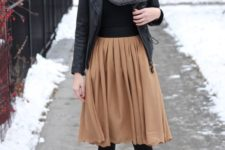 25 tan knee skirt, a black leather jacket and boots, a grey blanket scarf and a hat