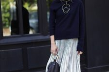 29 pleated midi, sneakers, a navy sweater and a statement necklace
