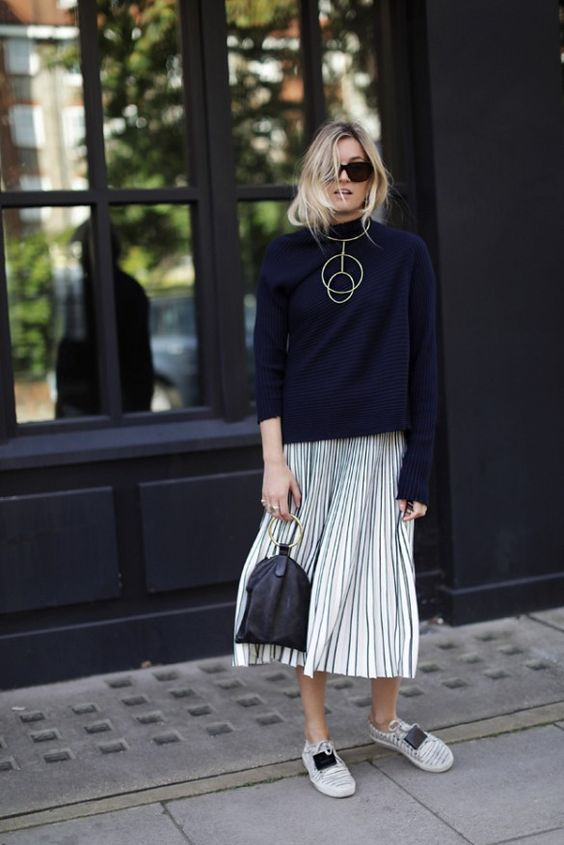 pleated midi, sneakers, a navy sweater and a statement necklace