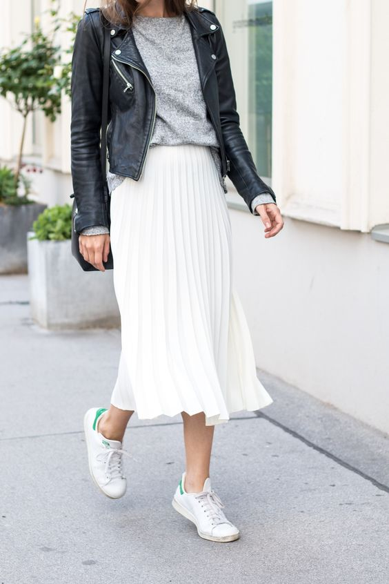 sporty look with a white pleated skirt and sneakers, a grey top and a black leather jacket