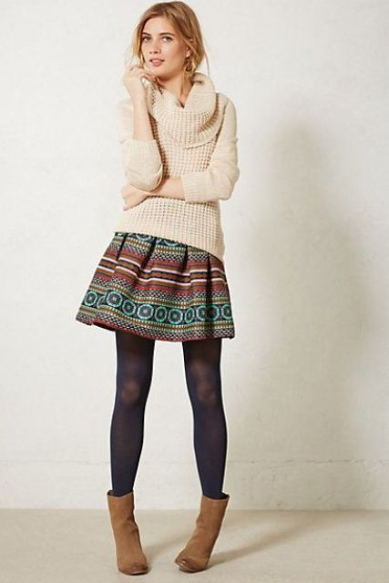 With beige sweater, black tights and brown ankle boots