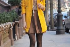 With beige top and pleated mini skirt, black tights and heels