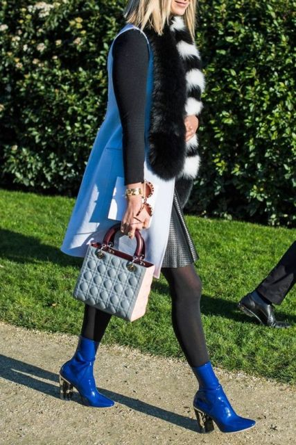 With black shirt, printed skirt, long vest with fur and small bag