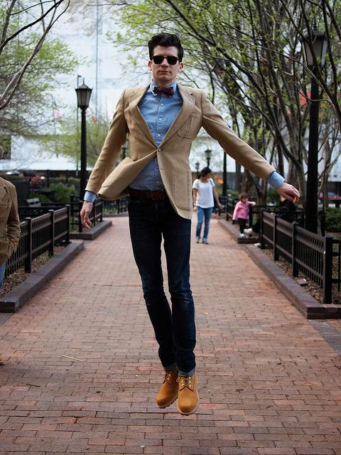 With blue shirt jeans camel jacket and bow tie
