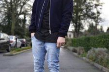 With distressed jeans, black shirt and jacket