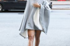 With gray poncho and statement necklace