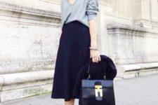 With gray shirt, midi skirt and black bag