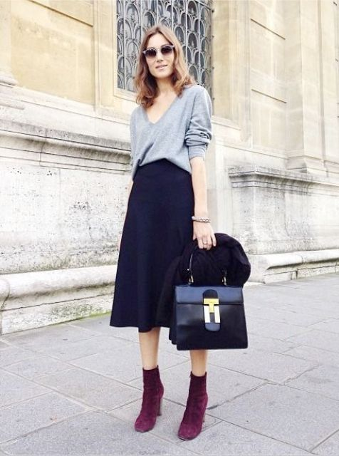 With gray shirt, midi skirt and black bag
