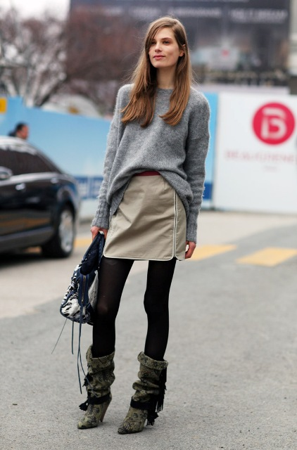 With gray sweater, mini skirt, black tights and leather bag