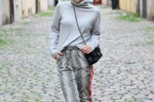 With gray turtleneck, chain strap bag and pumps