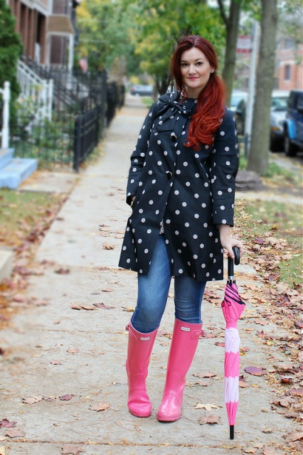 Fashionable rainy day outfit with jeans, pink wellies and colored umbrella